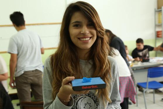 estudante com peça impressa 3D em PLA